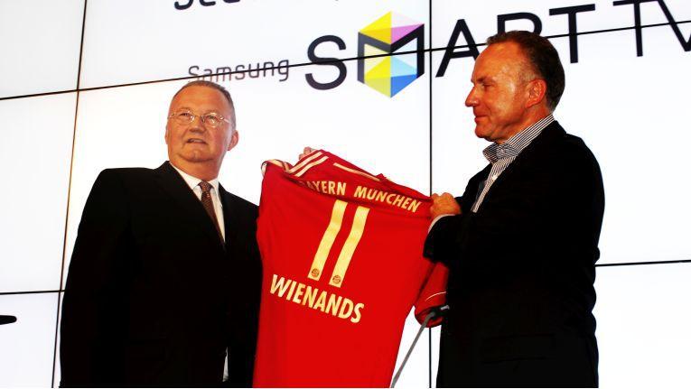 Karl-Heinz Rummenigge, Vorstandsvorsitzender des FC Bayern München (rechts) überreicht 2011 Hans Wienands, Senior Vice President bei Samsung Electronics ein Bayern-Trikot mit der Nummer 11 zur Besiegelung der Partnerschaft des Elektronikkonzerns mit dem Rekordmeister.