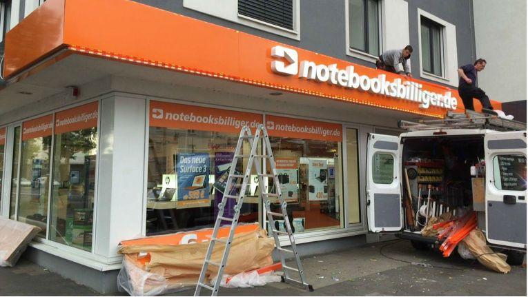 Nach dem Rückzieher der Stadt Düsseldorf bringen Arbeiter eine Leuchtreklame am Store von Notebooksbilliger.de an